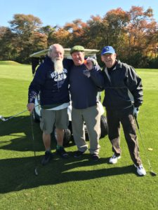 A photo of a group of people smiling for a picture at the golf outing.