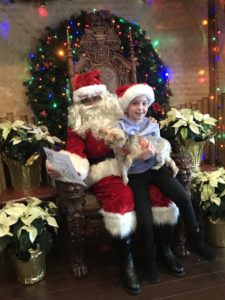 A young girl taking a photo with Santa