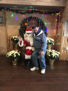 A man smiling for a photo with Santa.