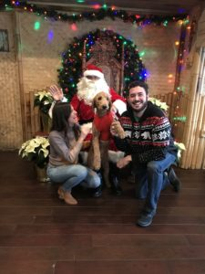 A young couple and their dog posing for a photo with Santa