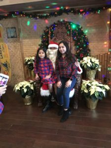 Two young girls taking a photo with Santa