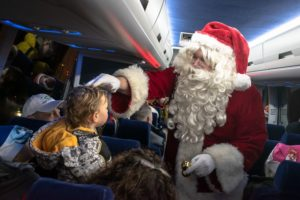 A photo of Santa greeting children on a bus.