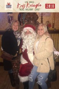 Two women posing for a photo with Santa.