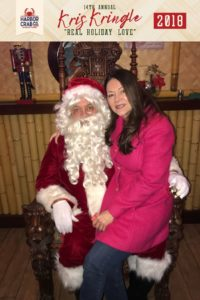 A photo of a woman posing with Santa.