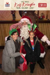 A mother and daughter posing for a photo with Santa.