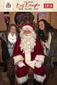 Two young girls posing for a photo with Santa.