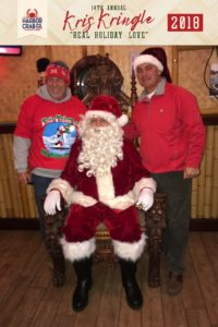 Two men posing for a photo with Santa.