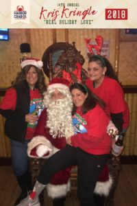 Three women posing for a photo with Santa.