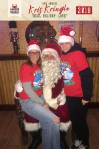 A mother and son posing for a photo with Santa.