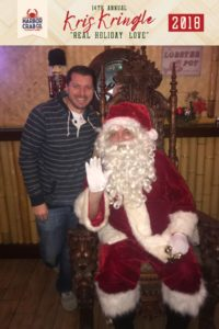 A man posing for a photo with Santa.