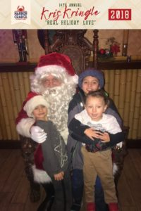 Three kids posing for a photo with Santa.