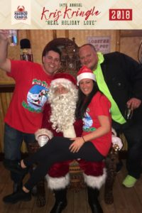 Three people posing for a photo with Santa.