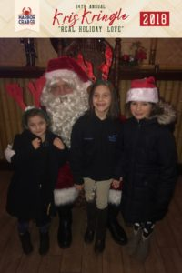 Three children posing for a photo with Santa.