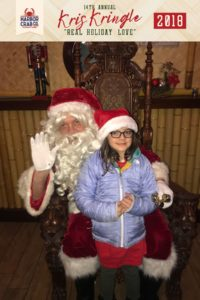 A child posing for a photo with Santa.