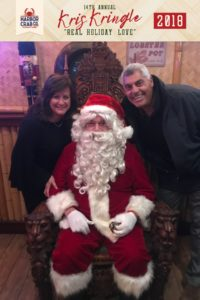 A woman and man posing for a photo with Santa.