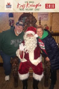 A man and woman posing for a photo with Santa.