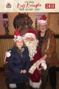 A young girl and woman posing for a photo with Santa.