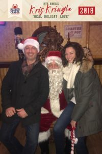 A couple posing for a photo with Santa.