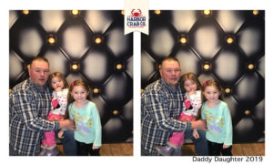 A photo of a father and two daughters smiling for the Daddy Daughter 2019 event.