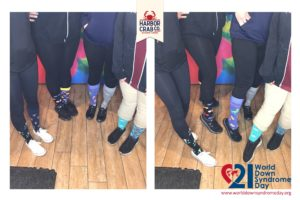 A photo of people's feet in mismatched socks.