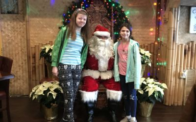 Two young girls taking a photo with Santa.